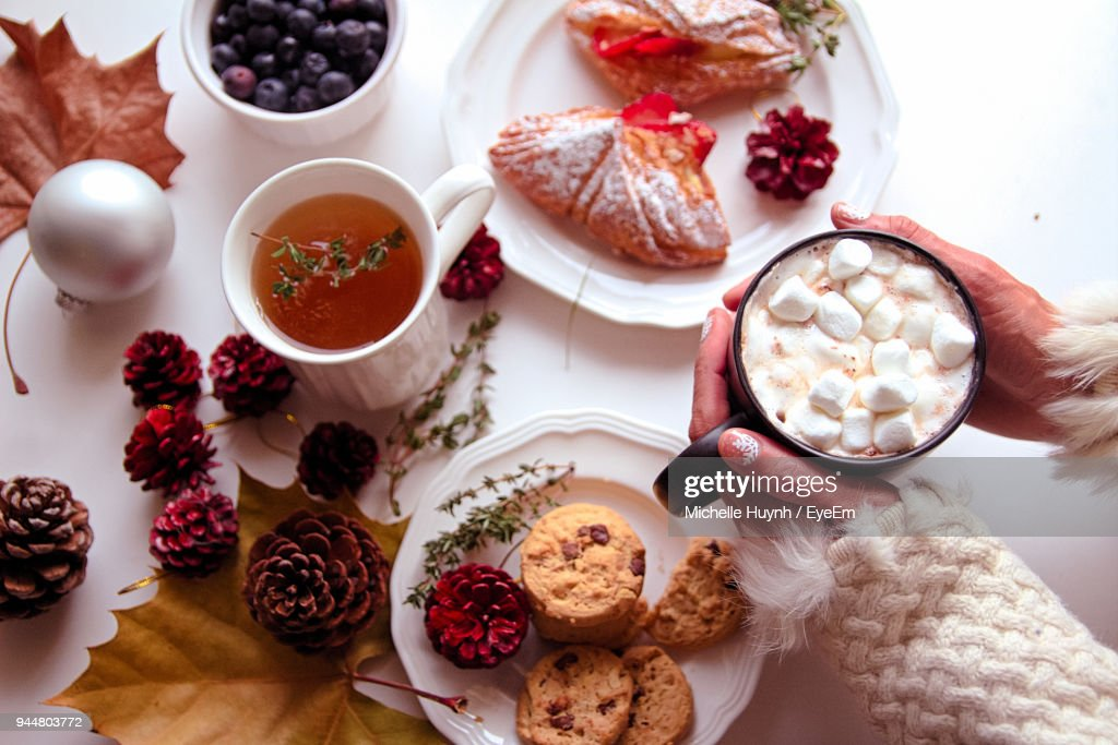 High Angle View Of Woman Holding Hot Chocolate Over Food Table : Stock Photo