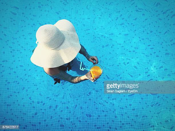 high angle view of woman holding juice glass in swimming pool - blue hat stock pictures, royalty-free photos & images