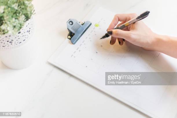 high angle view of woman holding pen over calendar on table - human body part stock pictures, royalty-free photos & images