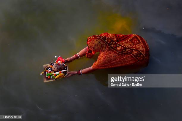 high angle view of woman holding religious offerings in lake - place of worship stock pictures, royalty-free photos & images