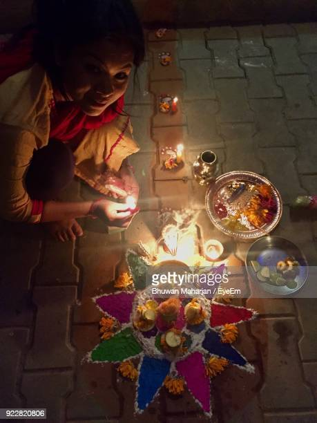 High Angle View Of Woman Igniting Candles