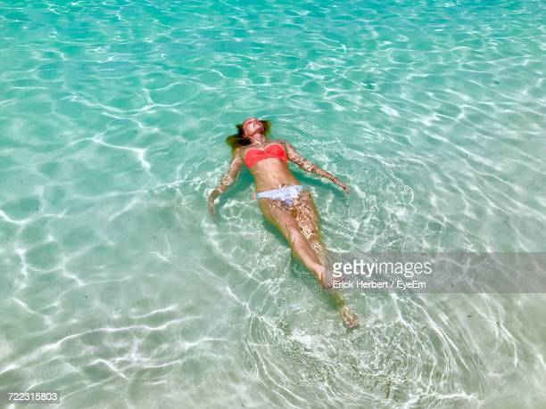 High Angle View Of Woman In Bikini Lying In Sea