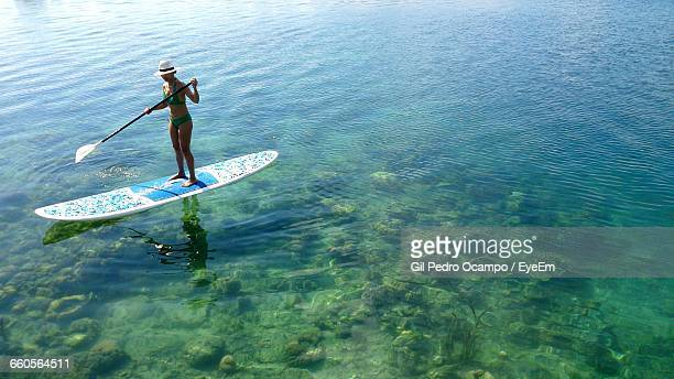 High Angle View Of Woman In Bikini Paddleboarding In Sea
