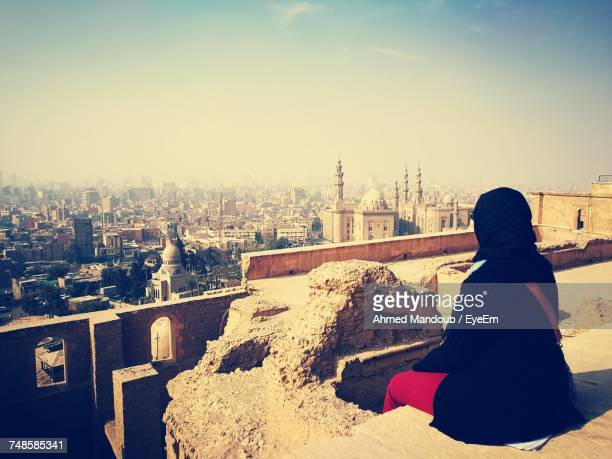 High Angle View Of Woman In Hijab Looking At Cityscape Against Sky