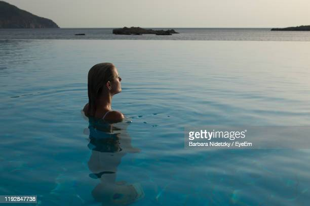 high angle view of woman in infinity pool against sea - lady barbara stock-fotos und bilder