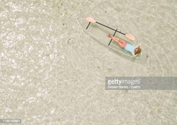 high angle view of woman in inflatable raft at sea - bortes stock pictures, royalty-free photos & images