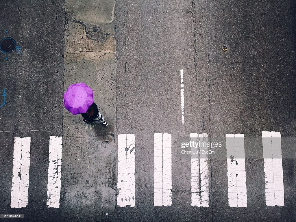 High Angle View Of Woman In Umbrella Walking On Road : Stock Photo