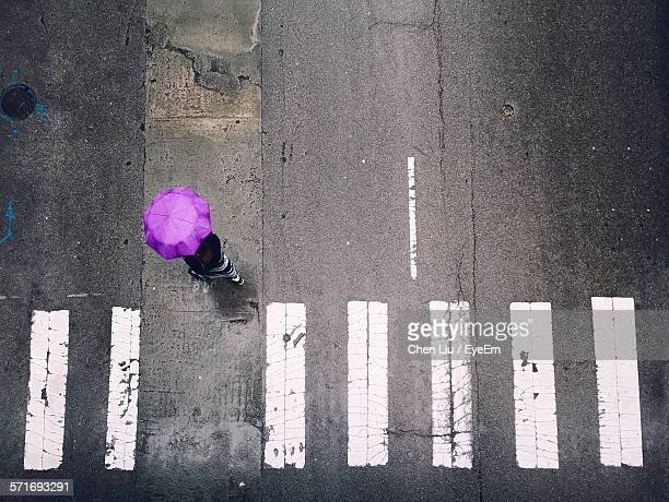 High Angle View Of Woman In Umbrella Walking On Road