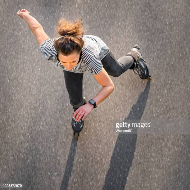 high angle view of woman inline skating on road during summer - active lifestyle stock pictures, royalty-free photos & images
