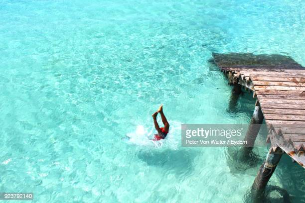 high angle view of woman jumping in sea - zanzibar island stock photos and pictures