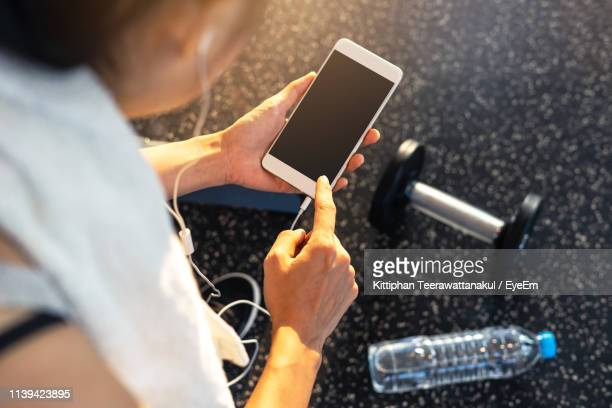 high angle view of woman listening music while using mobile phone over dumbbell and water bottle at gym - net sports equipment stock pictures, royalty-free photos & images