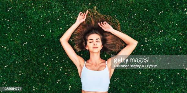 high angle view of woman lying down on grass - lying down stock-fotos und bilder