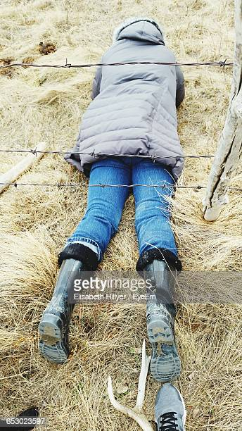 high angle view of woman lying down under barbed wire fence on field - metallic boot stock pictures, royalty-free photos & images