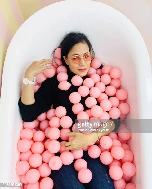 high angle view of woman lying on bathtub with pink color balls at home - spielball stock-fotos und bilder