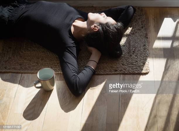 high angle view of woman lying on floor at home - home sweet home stock pictures, royalty-free photos & images