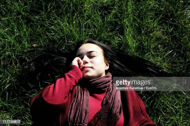 High Angle View Of Woman Lying On Grassy Field
