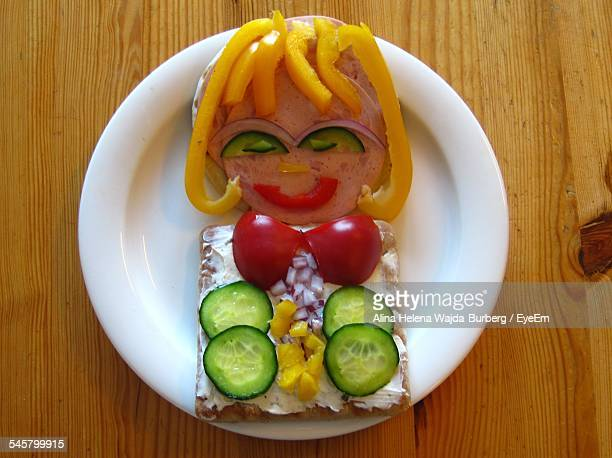 High Angle View Of Woman Made From Sandwich On Table