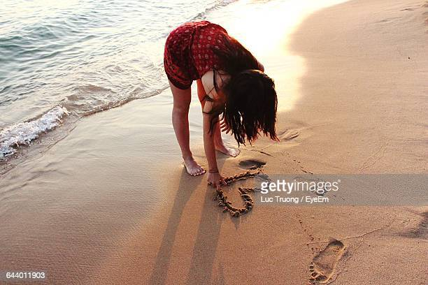 High Angle View Of Woman Making Heart Shape On Shore At Beach