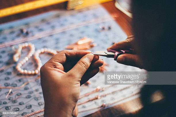 high angle view of woman making necklace - jewellery stock pictures, royalty-free photos & images