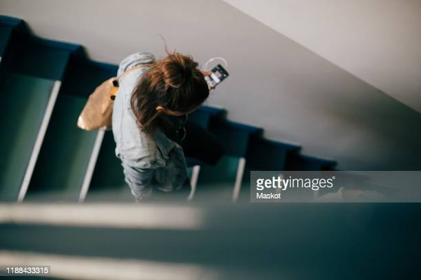 high angle view of woman moving down on stairs in apartment - staircase stock pictures, royalty-free photos & images