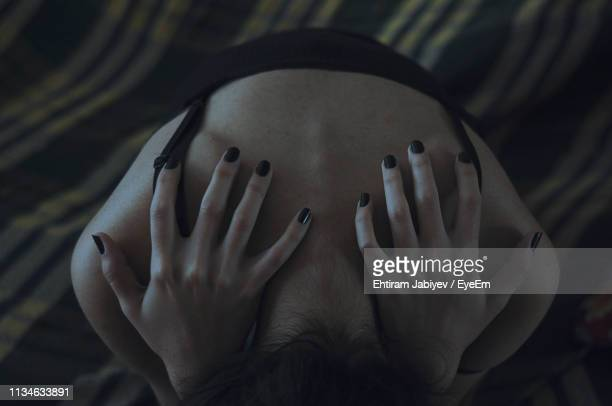 high angle view of woman on bed - black nail polish stock photos and pictures