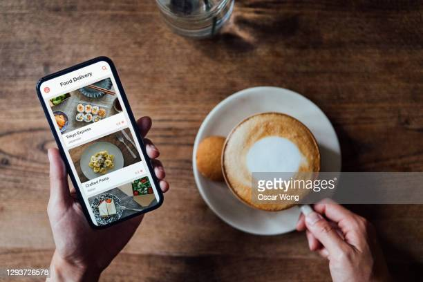 high angle view of woman ordering food delivery on smartphone while enjoying coffee - table stock pictures, royalty-free photos & images