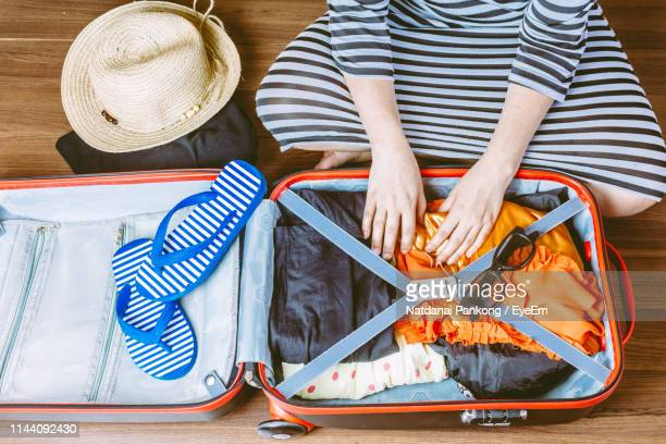 high angle view of woman packing suitcase while sitting on floor - packing stock pictures, royalty-free photos & images