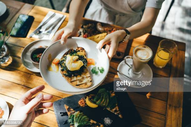 high angle view of woman passing platter of food to friend during brunch in an outdoor restaurant against beautiful sunlight - pase fotografías e imágenes de stock