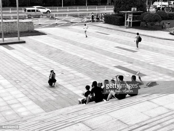 High Angle View Of Woman Photographing Badminton Players At Court