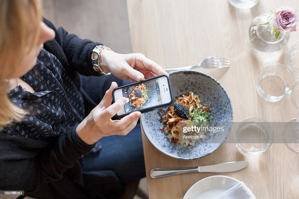 High angle view of woman photographing food through mobile phone in restaurant : Stock Photo