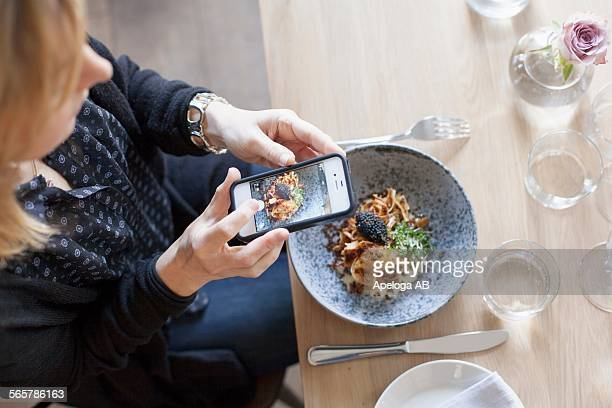 high angle view of woman photographing food through mobile phone in restaurant - photographing stock pictures, royalty-free photos & images
