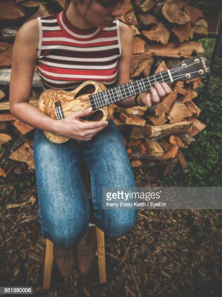 high angle view of woman playing guitar - kerry estey keith stock photos and pictures