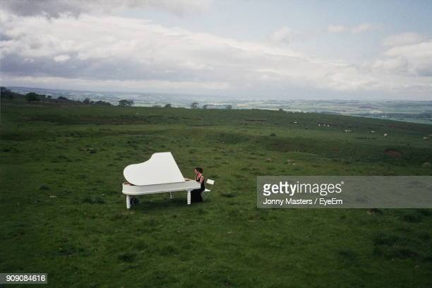 high angle view of woman playing piano at beach against sky - ピアノ ストックフォトと画像