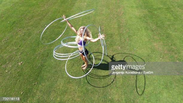 High Angle View Of Woman Playing With Plastic Hoops On Field During Sunny Day