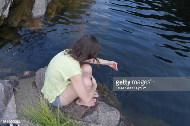 High Angle View Of Woman Playing With Water While Sitting On Rock At Lakeshore