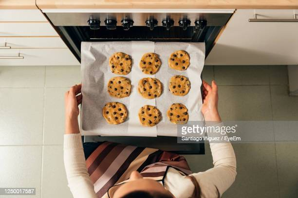 high angle view of woman preparing cookies in kitchen - baking sheet stock pictures, royalty-free photos & images