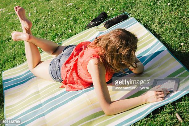 High Angle View Of Woman Reading In Digital Tablet While Lying At Park