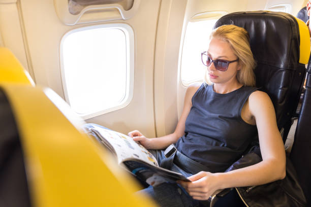 High Angle View Of Woman Reading Magazine Sitting At Plane
