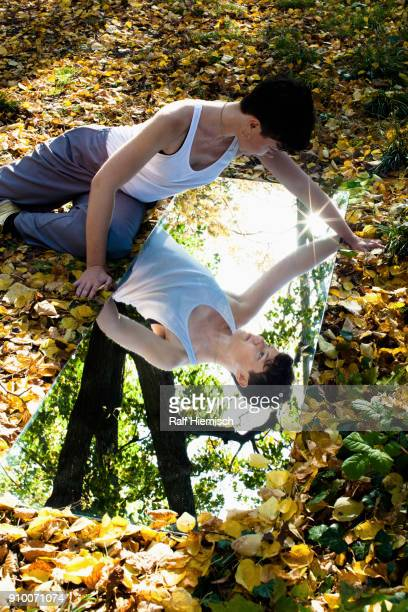 High angle view of woman reflecting in mirror while sitting on dry leaves at park during autumn