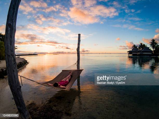 high angle view of woman relaxing on hammock in sea at sunset - polinesia francesa fotografías e imágenes de stock