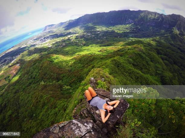 High angle view of woman relaxing on mountain cliff