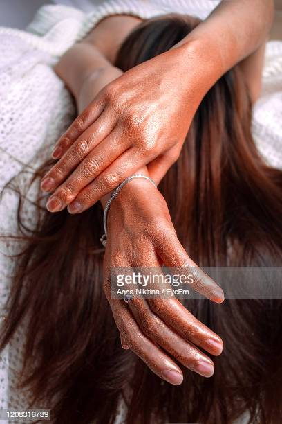 high angle view of woman resting on bed with painted hands - nikitina stock pictures, royalty-free photos & images