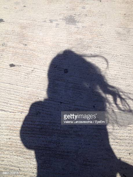 High Angle View Of Woman Shadow On Footpath