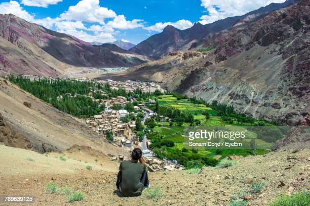 High Angle View Of Woman Sitting Against Mountains And Sky