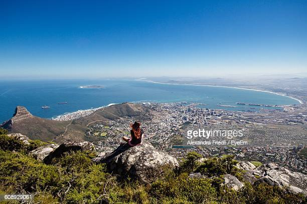 High Angle View Of Woman Sitting At Table Mountain Against Clear Blue Sky