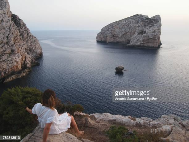 High Angle View Of Woman Sitting On Cliff Against Sea