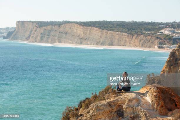 high angle view of woman sitting on cliff against sea - faro stock photos and pictures