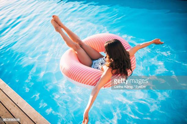 high angle view of woman sitting on inflatable ring floating in swimming pool - piscina pubblica all'aperto foto e immagini stock