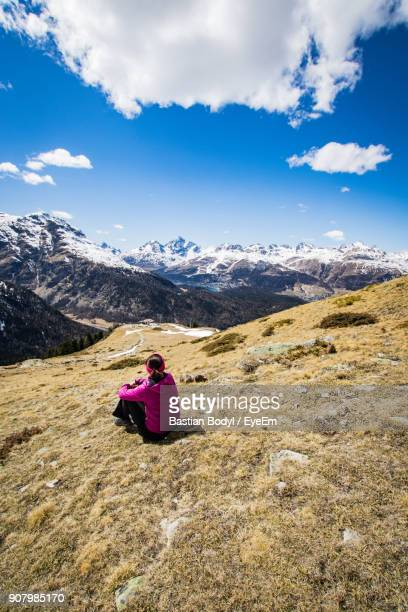High Angle View Of Woman Sitting On Mountain During Winter
