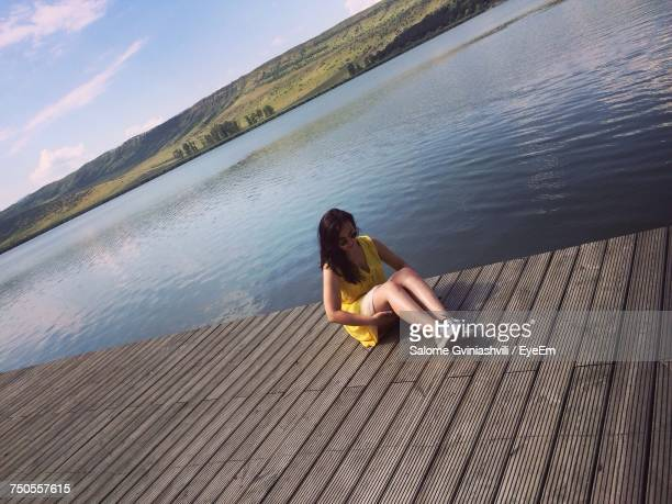 High Angle View Of Woman Sitting On Pier By Lake
